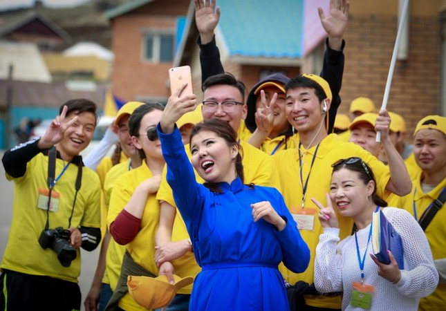 Former pop singer and parliamentary candidate Nara (C) taking selfies with people during a campaign event in Ulan Bator ahead of parliamentary elections.