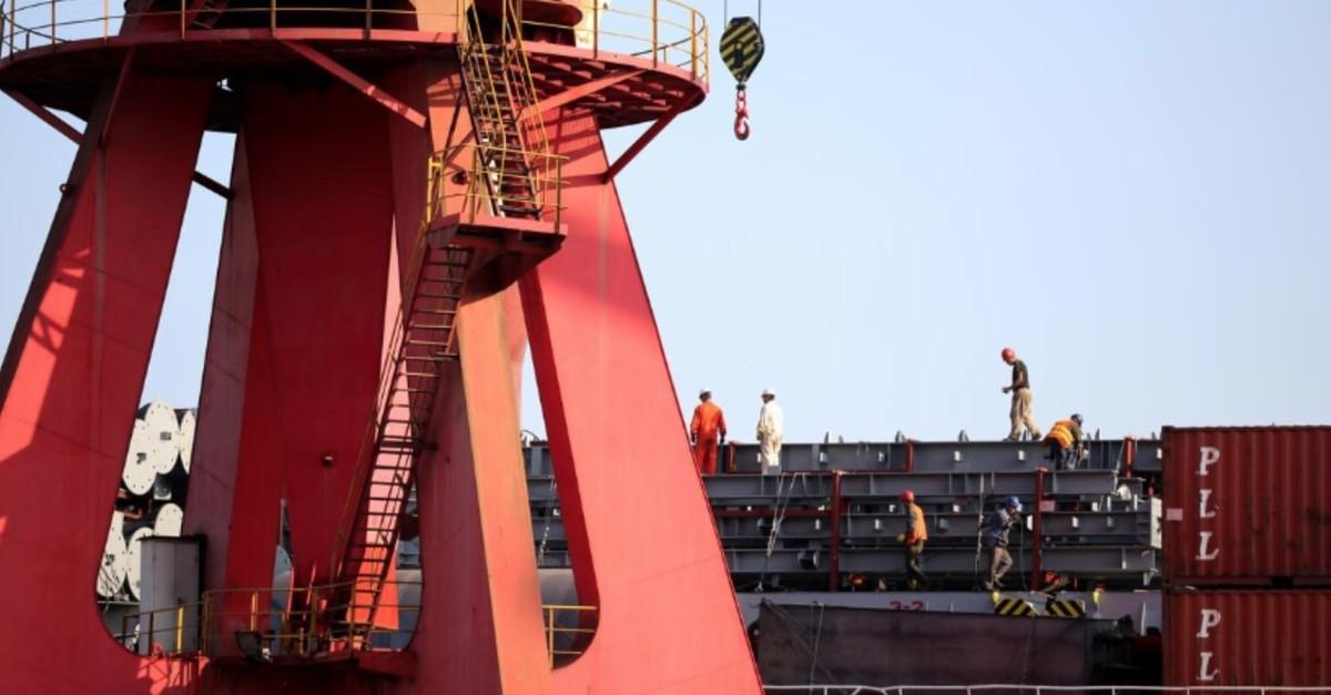 Men work on a cargo ship at a port in Lianyungang, Jiangsu province, China, Sept. 13, 2019.