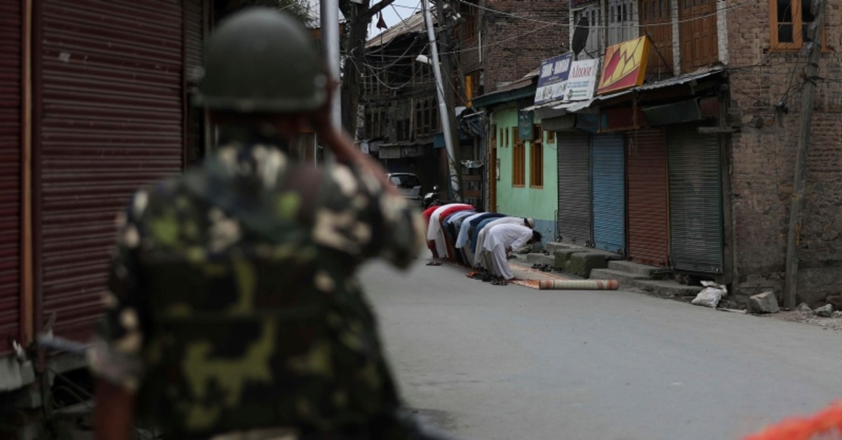 An Indian paramilitary soldier stands guard as Kashmiri Muslims offer Friday prayers on a street outside a local mosque during curfew like restrictions in Srinagar, India, Friday, Aug. 16, 2019. (AP Photo)