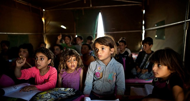 Syrian refugee children attend a class at a makeshift school set up in a tent at an informal tented settlement near the Syrian border on the outskirts of Mafraq, Jordan.(AP Photo)
