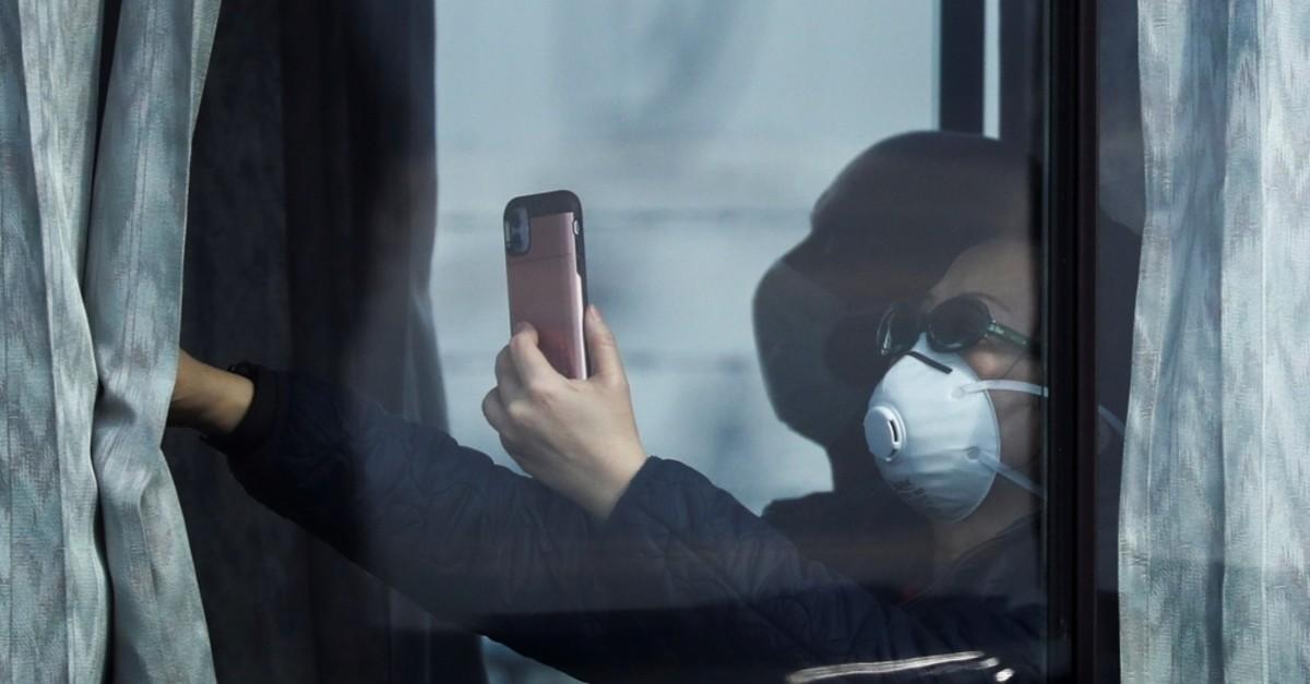 A passenger wearing a mask takes pictures as she leaves the coronavirus-hit cruise ship Diamond Princess at Daikoku Pier Cruise Terminal in Yokohama, south of Tokyo, Japan, Feb. 22, 2020. (Reuters Photo)