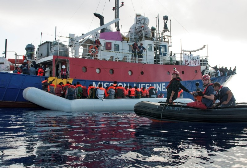 In this photo taken on Thursday, June 21, 2018, the ship operated by the German NGO Mission Lifeline rescues migrants from a rubber boat in the Mediterranean Sea in front of the Libyan coast. (AP Photo)