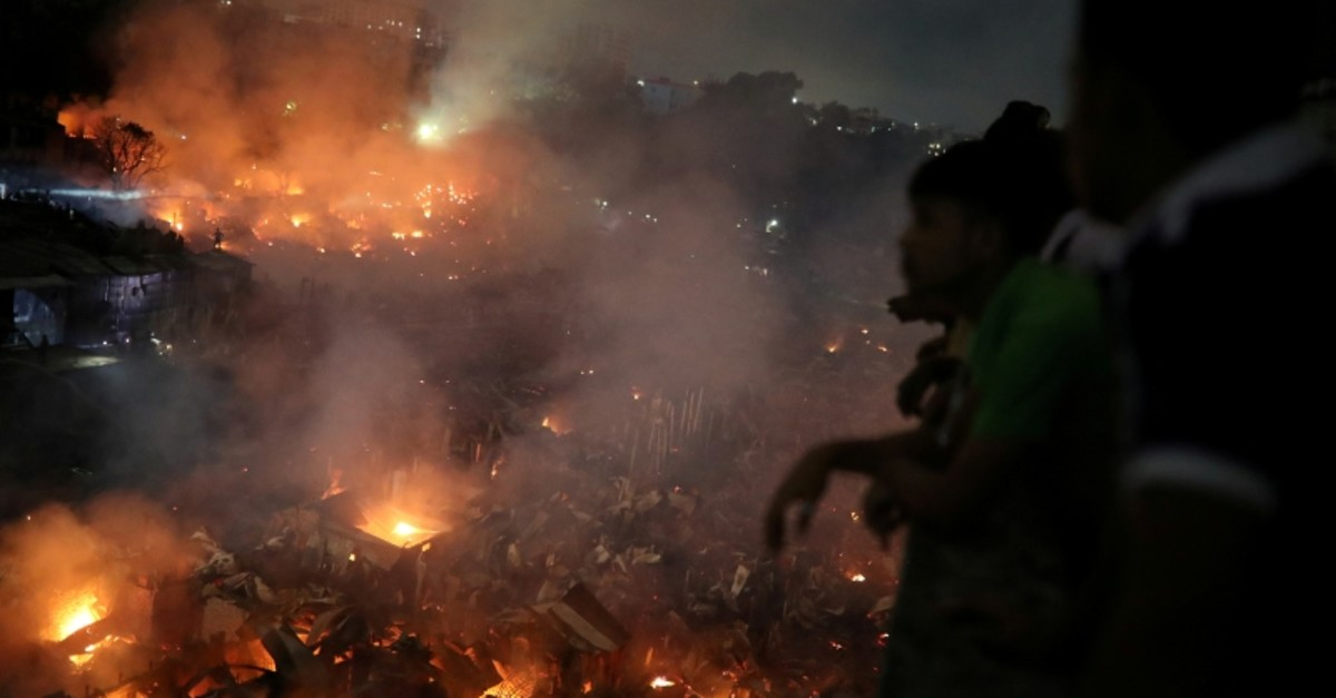 People gather at a rooftop to watch the fire that broke out at a slum in Dhaka, Bangladesh, August 16, 2019. (Reuters Photo)