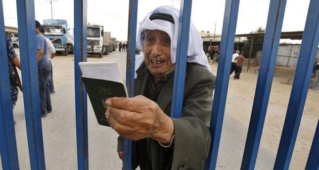 A Palestinian man holds his passport as he waits to cross into Egypt through the Rafah border crossing in the southern Gaza Strip June 27, 2009 ( File Photo)