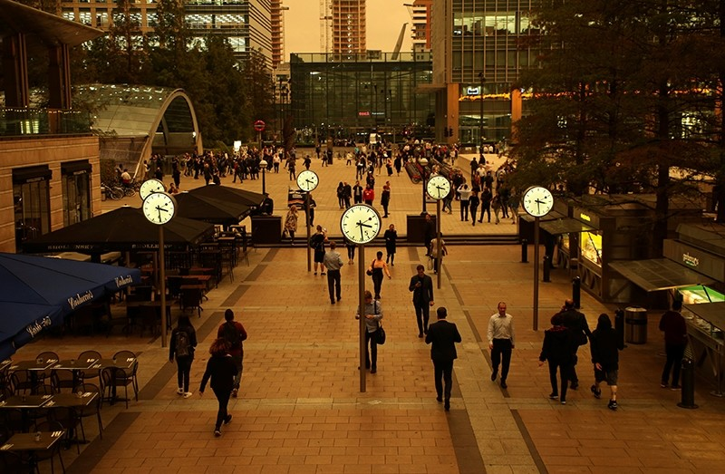 People walk through Canary Wharf while the sky overhead turns red as dust from the Sahara carried by storm Ophelia filters sunlight over London, Britain, October 16, 2017.