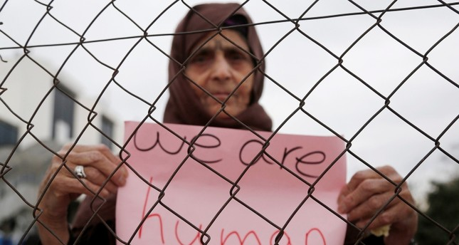 امرأة خلال وقفة احتجاجية على تردي أوضاع اللاجئين في المخيمات في اليونان (EPA)