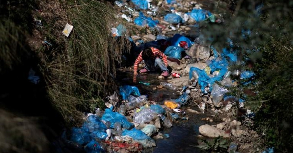 A child searches for his marbles among garbage at a makeshift camp surrounding the Moria migrant camp on the island of Lesbos, Greece, Feb. 18, 2020. (Reuters Photo)