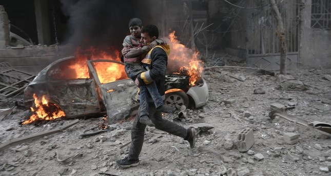 A Syrian paramedic carries an injured child following a reported bombardment by the Syrian regime in opposition-held Hamouria, eastern Ghouta, Jan. 6, 2018.