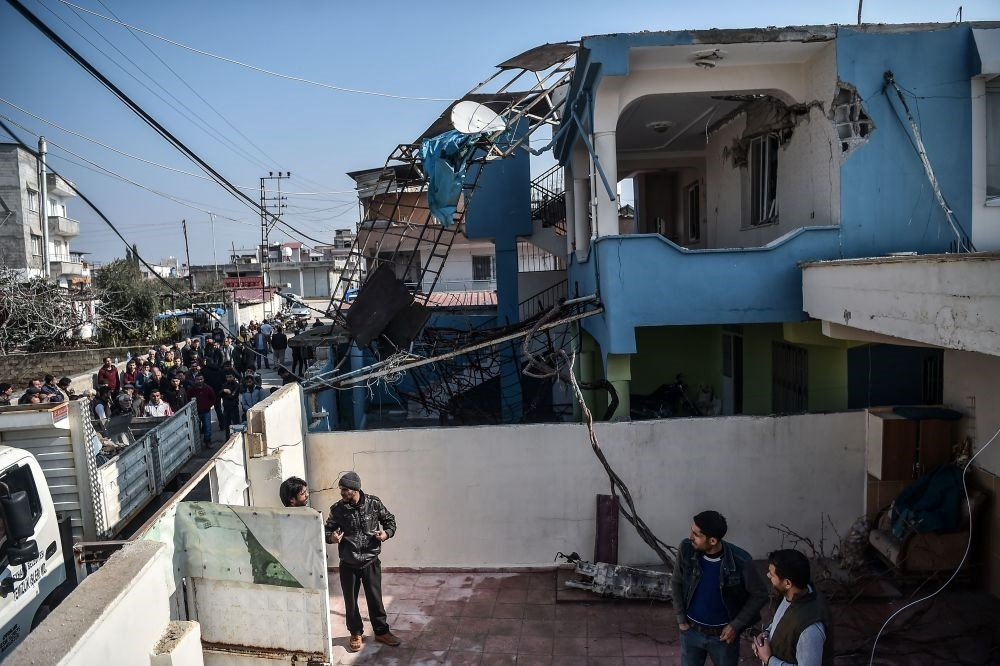 People gather in front of a house after it was hit by a rocket by YPG on Jan. 31, 2018 in the Reyhanlu0131 district of Hatay that killed a 17-year-old girl. (AFP Photo)