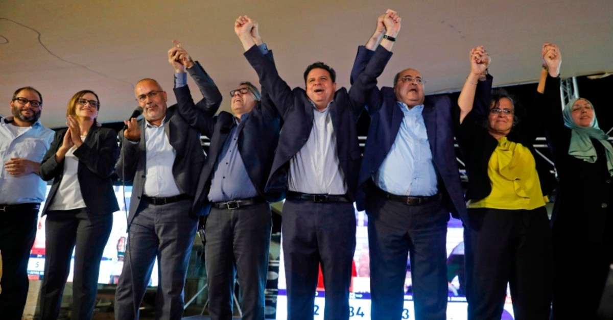 Joint List candidates celebrate before supporters at the alliance's campaign headquarters in the northern Israeli city of Nazareth on September 17, 2019, as the first exit polls are announced on television. (AFP Photo)