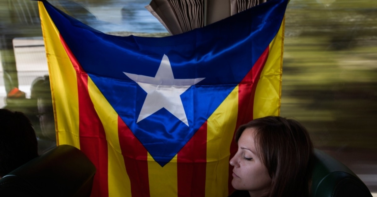 A Catalan pro-independence demonstrator sits in a bus, next to ,estelada,, or separatist flags, as they travel from Barcelona to Madrid, Spain, Saturday, March 16, 2019. (AP Photo)