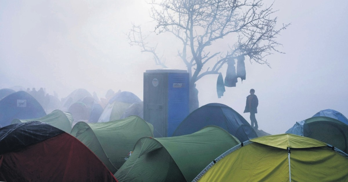 A migrant boy stands among tents during a foggy morning at a makeshift camp at the Greek-Macedonian border near the Greek village of Idomeni on March 8, 2016.