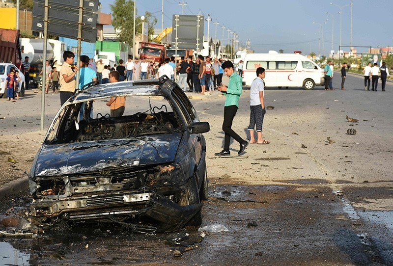 Iraqis check the damage at the site of an attack involving a moped laden with explosives against a convoy carrying an Iraqi election candidate in the city of Kirkuk on April 15, 2018. (AFP Photo)