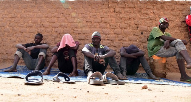 """Migrants from West Africa waiting in a room at a """"ghetto"""" in Agadez, northern Niger, as they wait to go to Libya from where they will attempt to reach Europe by  crossing the Mediterranean sea."""
