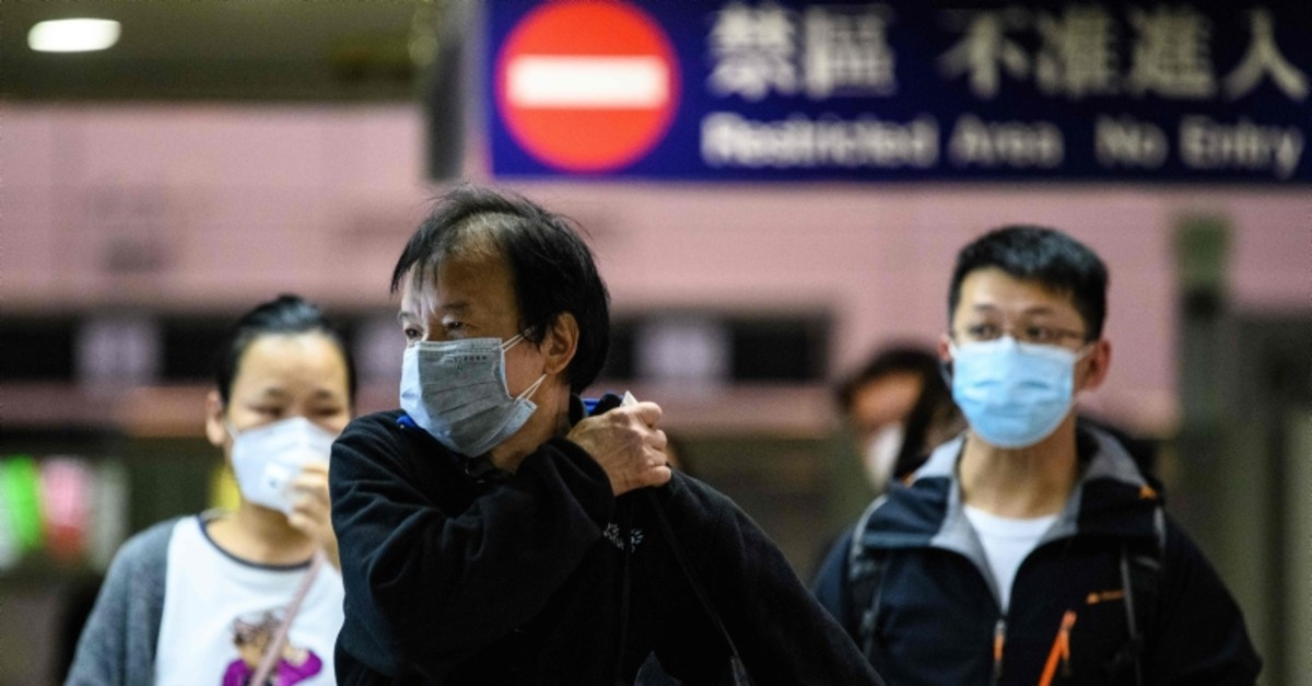 Passengers wear protective face masks  as they arrive from Shenzhen to Hong Kong at Lo Wu MTR station, hours before the closing of the Lo Wu border crossing in Hong Kong (AFP Photo)
