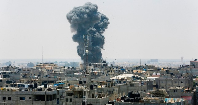 A picture taken on July 14, 2018 shows a smoke plume rising following an Israeli air strike in the southern Gaza Strip city of Rafah, near the border with Egypt. (AFP Photo)