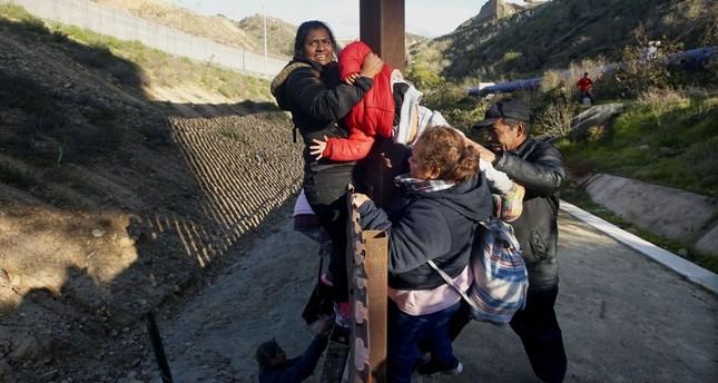Honduran migrants climb over the U.S.-Mexico border fence along on Jan. 6, 2019 in Tijuana, Mexico AFP Photo
