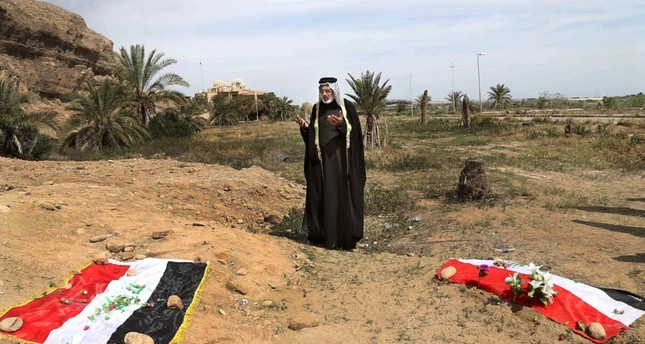 In this April 3, 2015 file photo, an Iraqi man prays for his slain relative, at the site of a mass grave, believed to contain the bodies of Iraqi soldiers killed by DaeshemAP Photo/em