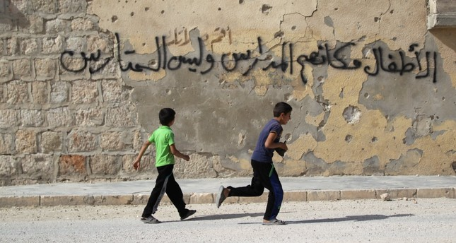 Boys run near graffiti on a riddled wall, in the opposition-controlled area of Maaret al-Numan town in Idlib province on May 26. The graffiti reads in Arabic: Children should be placed in schools, not barricades.