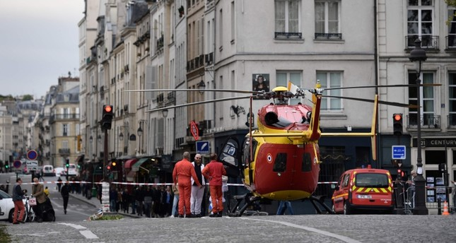 Emergency personnel stand near an air ambulance helicopter on the Pont Marie near Paris prefecture de police (police headquarters) after three persons have been hurt in a knife attack on Oct. 3, 2019. (AFP Photo)
