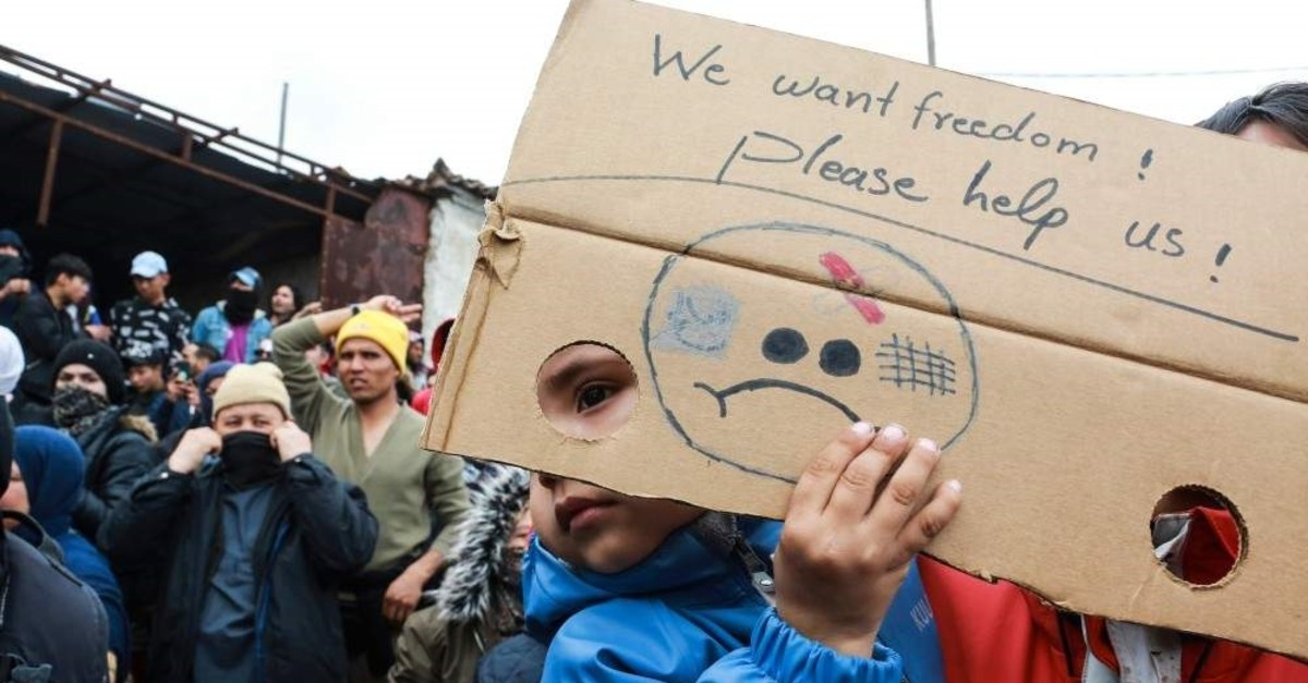 A child holds a poster during a demonstration of refugees and migrants outside the Kara Tepe camp, on the island of Lesbos, on Feb. 3, 2020. (AFP)