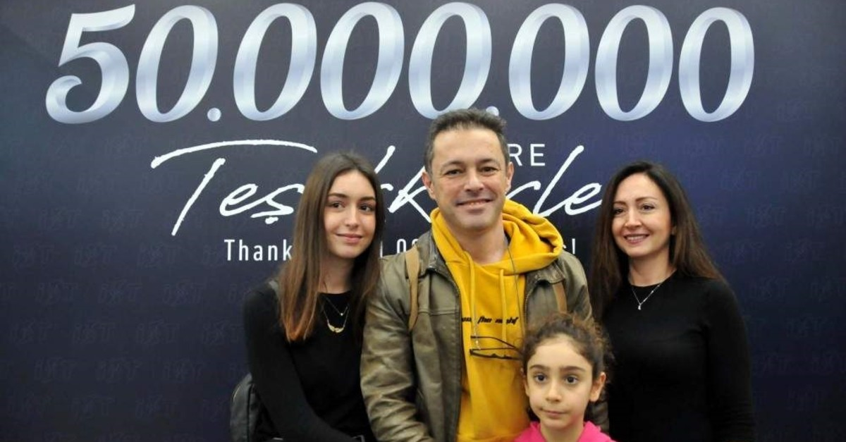 The Kobanbay family poses in front of a sign marking the 50 millionth passenger at the airport. (DHA Photo)