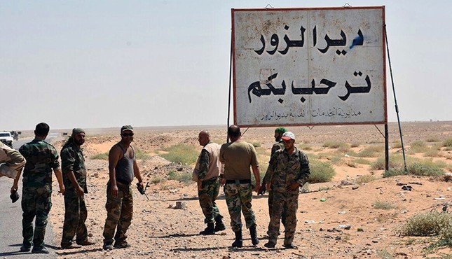 This photo released Sept. 3, 2017 by the Syrian official news agency SANA, shows Syrian troops and pro-regime gunmen standing next to a placard in Arabic which reads, Deir el-Zour welcomes you, Deir el-Zour, Syria. (SANA via AP)