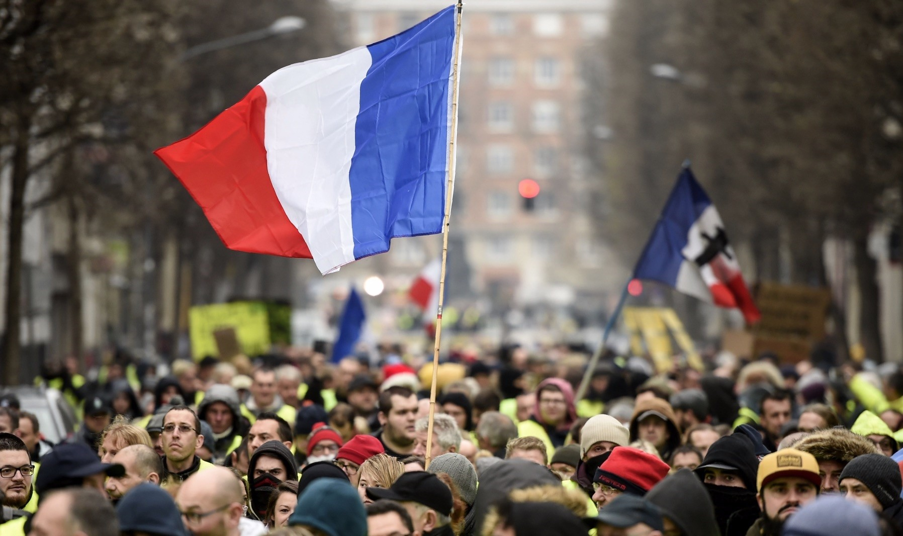 People hold up the French flag during a ,yellow vest, demonstration in the northern French city of Lille, Dec. 29.