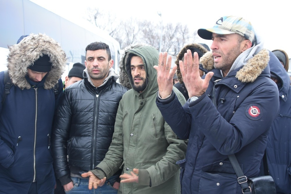 Palestinian migrant Qasim Amin (R), accompanied by other migrants, tells reporters their plight on the Greek side of the border.
