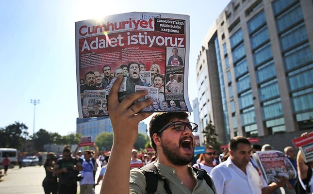 Activists, one holding today's copy of the Cumhuriyet newspaper, march to the court in Istanbul, Monday, July 24, 2017. The newspaper headline reads in Turkish: We want justice. (AP Photo)