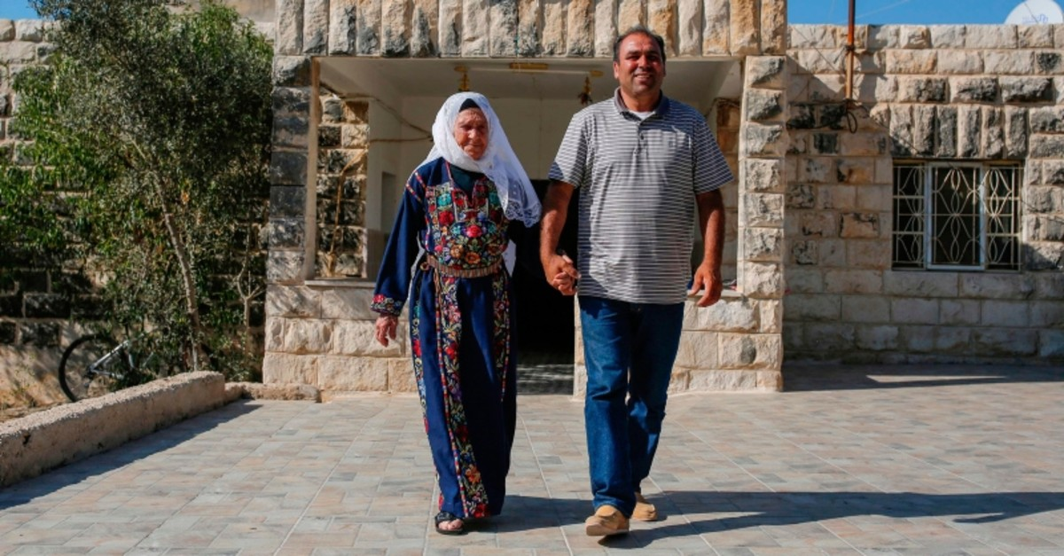 Muftia Tlaib, the maternal grandmother of U.S. Congresswoman Rashida Tlaib, walks with her son Bassam (R) outside their home in the village of Beit Ur al-Fouqa, in the occupied West Bank on August 15, 2019. (AFP Photo)
