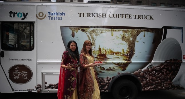 Girls in traditional Turkish attire offer Turkish coffee to New Yorkers.