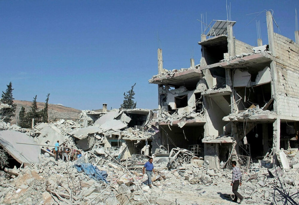 Residents search for survivors amid the rubble of a building following a reported overnight air-strike in Syria's Idlib on Sept. 30.