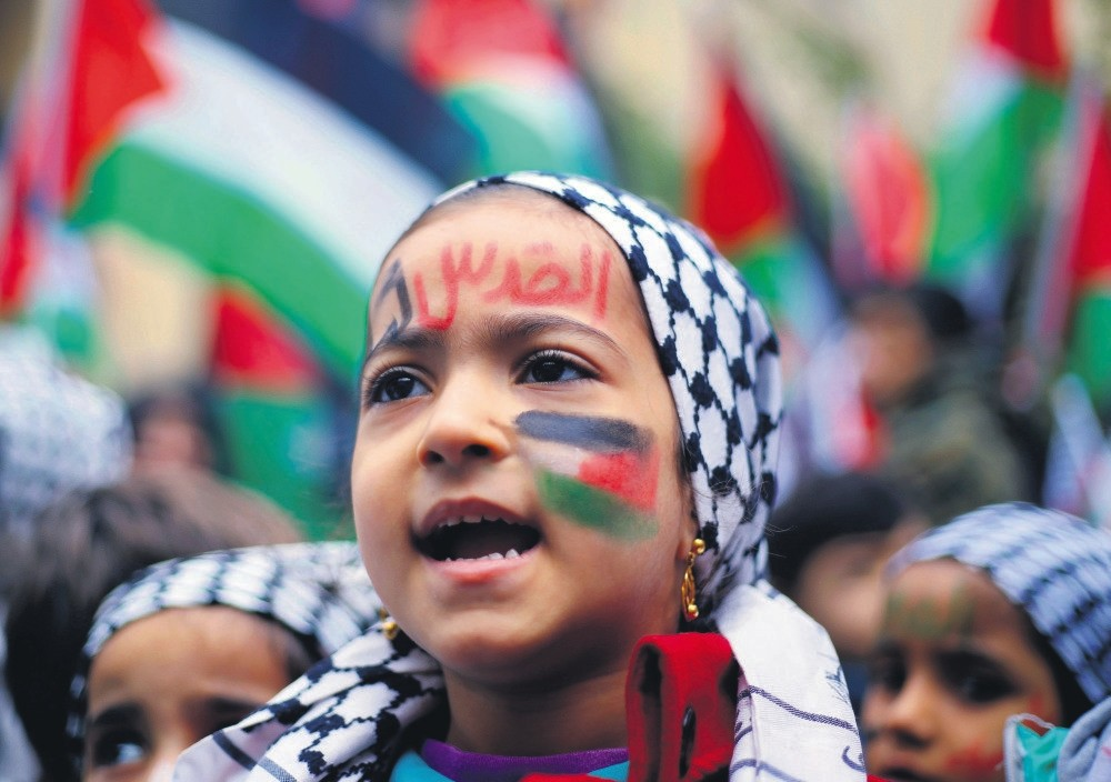 A girl with a Palestinian flag and ,Jerusalem is for us, painted on her face in Arabic, chants slogans during a sit-in in the Bourj al-Barajneh Palestinian refugee camp in Beirut, Lebanon Dec. 6.