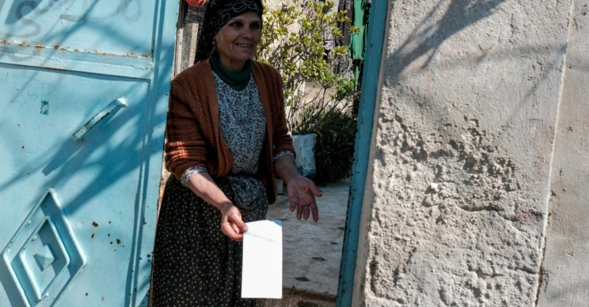 A woman shows the envelope left by the mysterious philanthropist, March 19, 2019.