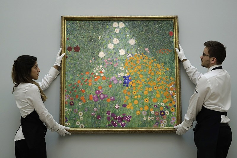 This is a Wednesday, Feb. 22, 2017, file photo of Sotheby's auction house staff as they pose for photographers with Austrian artist Gustav Klimt's ,Bauerngarten (Blumengarten), during a photocall at their premises in London. (AP Photo)