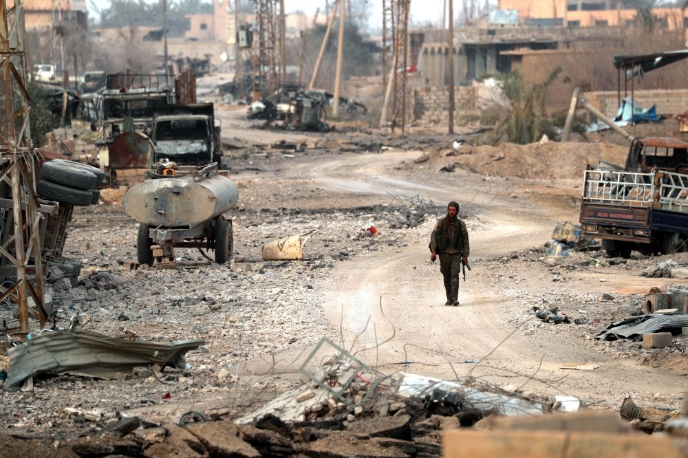 A member of a local radical group, who joined the YPG-dominated SDF forces, walks amid debris in the Syrian village of Baghouz, Jan. 27, 2019.