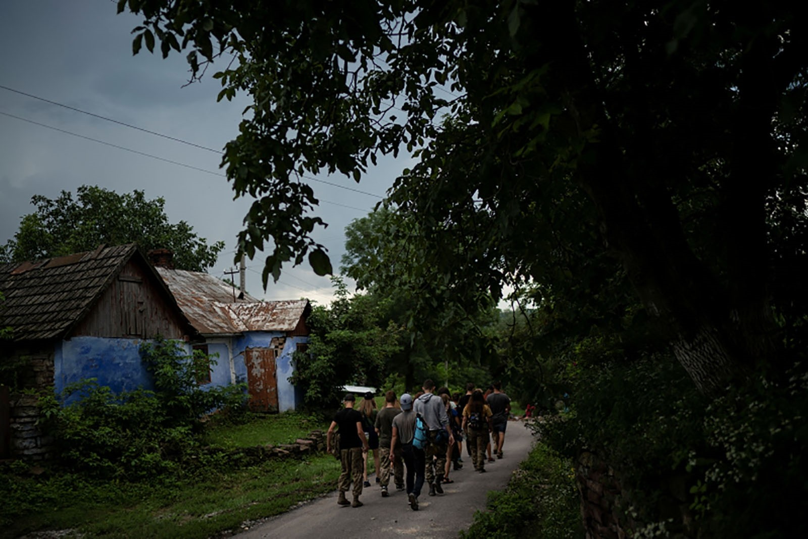 Young participants of the camp walk to a campsite in a village.