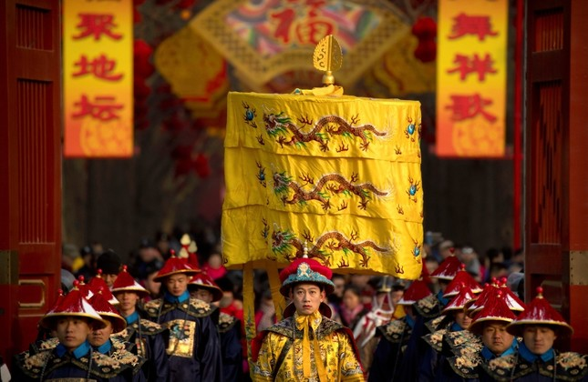 A performer dressed as an emperor, center, participates in a Qing Dynasty ceremony in which emperors prayed for good harvest and fortune at a temple fair in Ditan Park in Beijing, Tuesday, Feb. 5, 2019. (AP Photo)