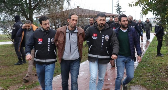 Police officers escort Tuncer Ustael to the courthouse in Kocaeli in this undated photo. ?HA Photo