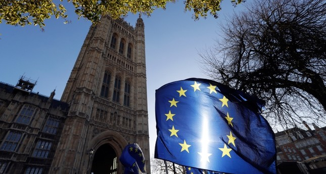 In this Jan. 22, 2019, file photo, the sun shines through European Union flags tied to railings outside parliament in London. AP Photo