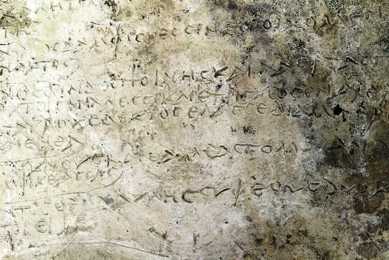 A handout photo made available by the Greek Ministry of Culture shows a clay tablet with an engraved inscription discovered after three years of excavations in the archaeological site of Ancient Olympia.