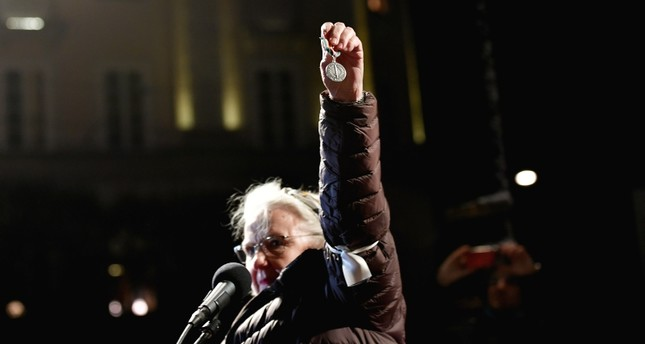 Doctare holds the medal she received while working for U.N. Peacekeeping force in Bosnia in 1980s, wanting to return it, as a protest against the awarding of Handke during a demonstration in Stockholm TT News Agency/Stina Stjernkvist via REUTERS
