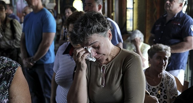 Orthodox faithful attend a memorial service for the victims of a forest fire, inside a church at Mati village, east of Athens, Sunday, July 29, 2018. (AP Photo)