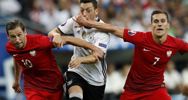Germany's Mesut Ozil, center, is challenged by Poland's Grzegorz Krychowiak, left, and Poland's Arkadiusz Milik during the Euro 2016 Group C soccer match. (AP Photo)