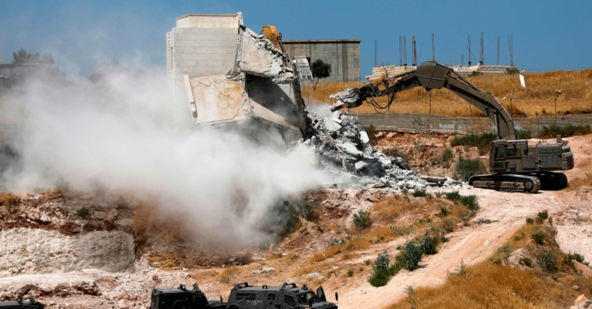 Israeli military machinery demolishes a Palestinian building in the village of Sur Baher which sits on either side of the Israeli barrier in East Jerusalem and the Israeli-occupied West Bank July 22, 2019. (AFP Photo)