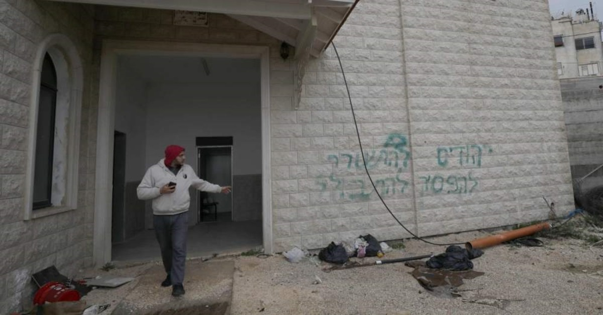 A man points at slogans sprayed on a mosque in the northern Israeli Arab village of Jish, also known as Gush Halav, Feb. 11, 2020. (AFP Photo)