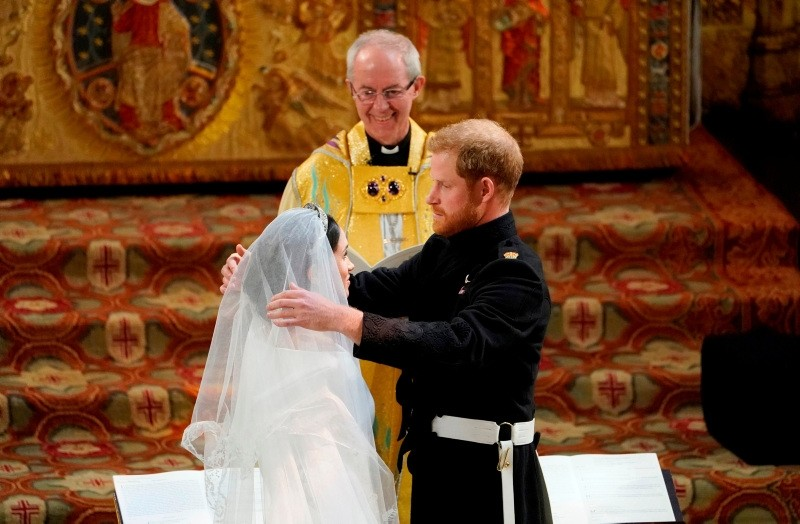 Britain's Prince Harry, Duke of Sussex (R) removes the veil of US actress Meghan Markle (L) as they stand at the altar together before Archbishop of Canterbury Justin Welby (C) in St George's Chapel, Windsor Castle, in Windsor, on May 19, 2018 during their wedding ceremony.