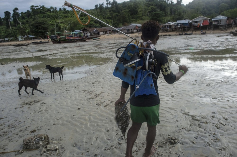 A Moken fisherman, heading home while carrying his fishing gear and a pufferfish he caught in Nyaung Wee village in the Myeik Archipelago, off the coast of southern Myanmar.
