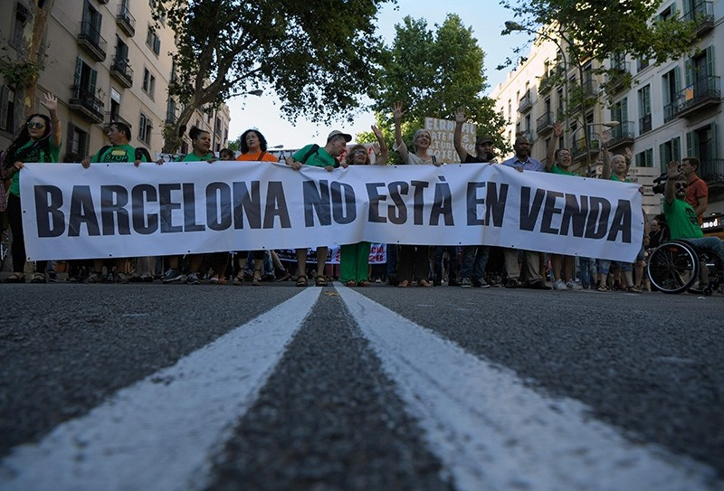 Protesters holds a placard that says: ,Barcelona is not for sale,  during a demonstration in Barcelona on June 10, 2017 against what they claim is a lack of control by the city's tourism management. (AFP Photo)